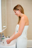 Washing hands. Young woman washing her hands in the bathroom Royalty Free Stock Image