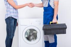 Washing. Handshake of housewife and repairman near the washing machine Stock Photo