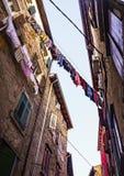 Washing hanging between mediterranean houses in a narrow street royalty free stock image