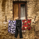 Washing hangs on a line in front of a half shuttered window in a brick wall of a Tuscan village in a square format. Stock Photos