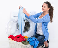 Washing. Happy young woman is doing laundry with washing machine at home Stock Image