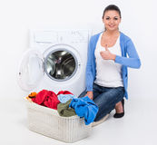 Washing. Happy young woman is doing laundry with washing machine at home Royalty Free Stock Photo