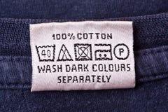 Washing instruction. Clothing label washing instruction tag on blue t-shirt stock photos