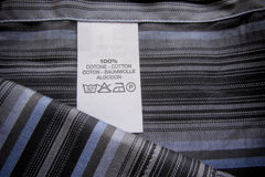 Washing instruction label on cotton vertical stripes shirt Royalty Free Stock Photos