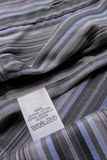 Washing instruction label on cotton vertical stripes shirt Stock Photography