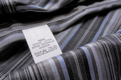 Washing instruction label on cotton vertical stripes shirt Royalty Free Stock Photo