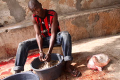 Washing Intestines after Eid Sheep Sacrifice. A man washes intestines in a bucket on the sidewalk outside his house in a neighborhood of Dakar, Senegal, after Royalty Free Stock Photos