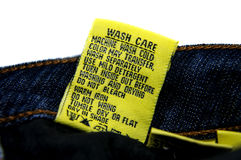 Washing Jeans Instructions. Yellow tag attached with the jeans informs washing instructions and guides royalty free stock photo