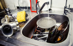Washing kitchen ware. A lot of dirty kitchen ware in a sink Stock Image