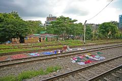 Washing laid out to dry on the hot ballast of the Burmese Railway in the suburbs of Yangon, Myanmar. City scenes on the railways in Yangon, the capital of Burma Royalty Free Stock Images