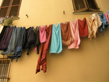 Washing line. Lots of colorful clothes and towels hanging on a washine line in front of a tuscan house wall Stock Photos