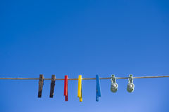 Washing Line Against Bright Blue Sky. Clothes pegs hanging off a washing line against a bright blue sky Stock Photo