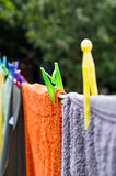 Washing line. Towels on washing line fastened with colorful plastic pesgs Royalty Free Stock Photos