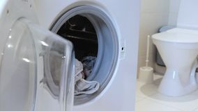 Washing linen and clothes concept, woman puts dirty clothes in washing machine and closes it.  stock footage