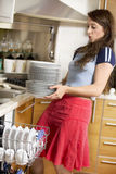 Washing-machine. Dishes are too heavy for her royalty free stock photo