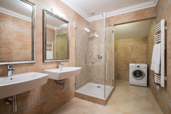 Washing machine in beige bathroom Stock Photos