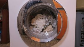 Washing machine spinning. Washing machine with clothes inside stock footage