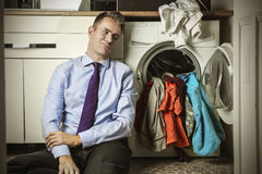 By the washing machine. Desperate businessman waiting by the washing machine Royalty Free Stock Photos