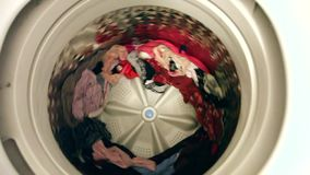 Washing machine drum spin. A clean load of clothes in a washing machine comes slowly to a stop from spinning stock video footage