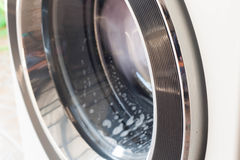 Washing machine full of dirty clothes. Stock Photo
