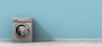 Washing Machine Full Single. A front view of a regular brushed metal washing machine filled with clothing in an empty room with a shiny tiled floor and a baby Royalty Free Stock Images