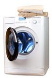 The washing machine with an open door and linen Stock Image