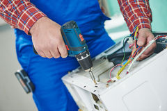 Washing machine repair. Repairer hands with screwdriver disassembling damaged unit for repair Royalty Free Stock Photo