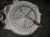 Washing machine tank with wrench - the process of removing the pulley stock photography