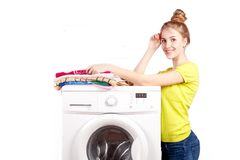 Beautiful happy girl and washing machine isolated on white background. Washing machine with towels and beautiful white girl smiling looking at camera over white royalty free stock photo
