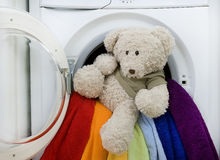 Washing machine, toy and colorful laundry to wash Stock Photos