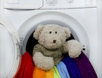 Washing machine, toy and colorful laundry to wash Stock Photography