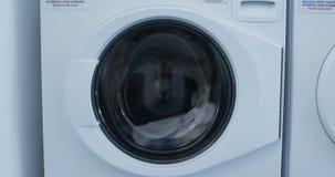 Washing machine washing clothes 4k. Washing machine washing clothes at laundromat 4k stock video footage