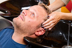 Washing man hair. In beauty parlour hairdressing salon Stock Image