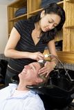 Washing a man's hair 1. Hair desser washing a man's hair at the salon 1 Royalty Free Stock Photography