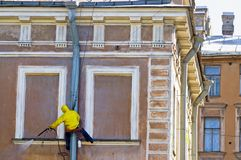 Washing old building facade. Cleaning service worker washing old building facade stock photo