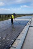 Washing the panels. Worker washing the photovoltaic panels on a roof Stock Images