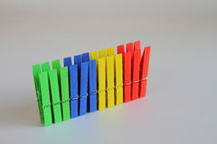 Washing pegs in primary colors against a white background Royalty Free Stock Photography