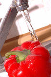 Washing pepper. Under the tap Stock Photos