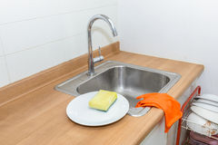 Washing plates with detergent and gloves Royalty Free Stock Images