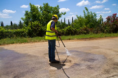 Washing the platform. Worker washing the industrial cement floor with a pressure washer Royalty Free Stock Photo