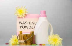 Washing powder and laundry softener on a gray. Washing powder, laundry softener, clothes pegs and flowers on a gray background Stock Image