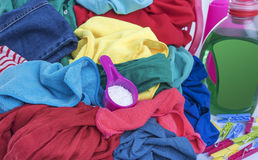 Washing powder and a pile of dirty laundry. Stock Images