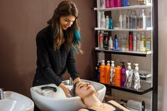 Washing procedure. Beautiful young woman with hairdresser washing head at hair salon stock images