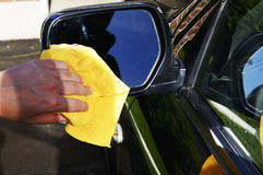 Washing rearview mirror. Woman's hand with microfiber cloth washing rear view mirror of an SUV car Royalty Free Stock Photo