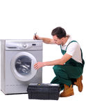 Washing. A repairman holding a spanner and posing next to a washing machine isolated on white background Stock Images