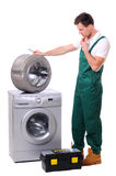 Washing. A repairman holding a spanner and posing next to a washing machine isolated on white background Royalty Free Stock Photos