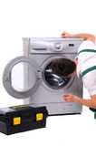 Washing. A repairman holding a spanner and posing next to a washing machine isolated on white background Royalty Free Stock Images