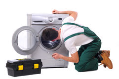 Washing. A repairman holding a spanner and posing next to a washing machine isolated on white background Stock Image