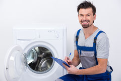 Washing. Repairman is repairing a washing machine on the white background Royalty Free Stock Photo