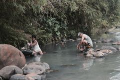 Washing in the river. Out in the villages in the Philippines people going about their daily lives in all different ways, for this couple it's time to do laundry Royalty Free Stock Photos
